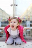 Little cute girl sits on floor, holds on to railings and shouts in mall.