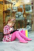 Little girl in pink sits on floor and looks at tablet pc near showcase with antiques at mall.