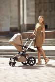 Trendy modern mother on a city street with a pram. Young mother walks with a child in the city. Beau