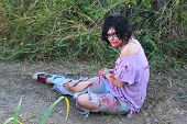 pic of gruesome  - A woman in bloody clothes pretends to be a zombie - JPG