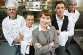 stock photo of waiter  - Cute female manager posing with the staff in a modern kitchen - JPG