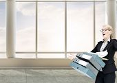 Composite image of businesswoman dropping many folders in bright 3d room with windows