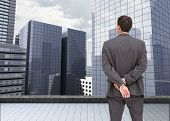 Composite image of businessman standing with hands behind back on the roof of building watching the city