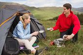 Happy couple cooking outdoors on camping trip in the countryside