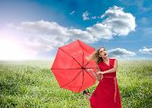 Composite image of beautiful woman wearing red dress holding umbrella standing on grass under sunny