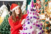 Beautiful female owner in Santa hat decorating Christmas tree at store