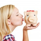 Blond young woman kissing a piggy bank with her lips