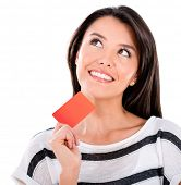 Thoughtful woman with a credit card - isolated over a white background