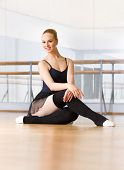 Ballerina does exercises sitting on the wooden floor in the classroom with barre and mirrors