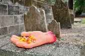 stock photo of prank  - A Halloween severed prank hand offers candy corn in the graveyard