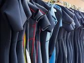 Line of Multiple Hanging Wetsuits
