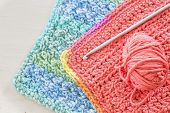 stock photo of crotch  - Two hand crotched dishcloths with a crotchet hook and ball of yarn - JPG