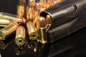 image of hollow point  - Various 9mm bullets and a loaded magazine isolated on a black reflective surface - JPG