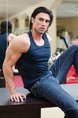 Handsome, Muscular Man Sitting On Desk