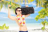 Happy guy with beer and boombox on his shoulder gesturing happiness on a tropical beach