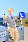Smiling mature man on his car holding a L sign and car key after having his driver's licence, outsid