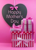stock photo of mummy  - Stack of beautiful pink stripe and polka dot present gifts with heart shape blackboard with Happy Mothers Day message - JPG