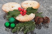 Christmas mince pie group with holly, green baubles, pine cones and winter greenery.