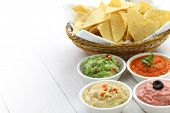 tortilla chips with four super bowl dips which are salsa roja, guacamole, taramasalata, and hummus.