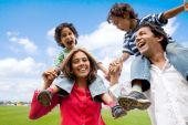 stock photo of piggyback ride  - happy family having fun in front of their house - JPG
