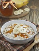 foto of porridge  - Porridge with bananas and honey in a bowl on the table - JPG