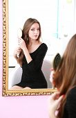 picture of dress-making  - Young beautiful woman making hairstyle near mirror - JPG