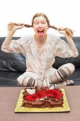 picture of sweet sixteen  - Happy teenager celebrating sweet sixteen birthday with chocolate cake laughing and pulling her pigtails - JPG