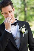 Handsome young groom biting nails in garden