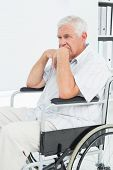 Side view of a sad senior man sitting in wheelchair at the medical office
