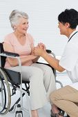 Side view of a doctor talking to a senior patient in wheelchair at the hospital