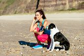 stock photo of breath taking  - Relaxed fitness woman with dog listening music with sport arm band and earphones at the beach - JPG