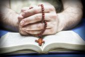 stock photo of piety  - Christian believer praying to God with rosary in hand - JPG