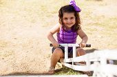 stock photo of seesaw  - Pretty Hispanic little girl having fun in a seesaw on a sunny day - JPG
