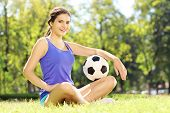 Young athlete female sitting on a green grass and holding a soccer ball in a park