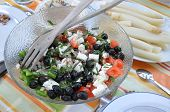 Salad consisting of olives, goat cheese, tomatoes, peppers, and herbs in front of a bowl of white asparagus