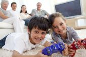Children Playing Video Games And Family On Sofa