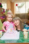 Little girl with her mother with a birthday cake on  birthday party