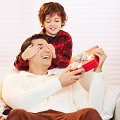 Son holding eyes of father with gift closed at christmas