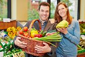 Happy couple buying fresh fruits and vegetables in organic food store