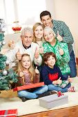 Happy family at christmas with gifts holding thumbs up
