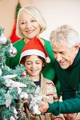 Happy grandparents decorating the christmas tree with their grandson