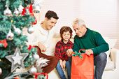 Boy with father and grandfather at christmas getting gifts