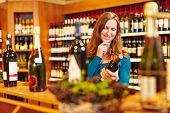 Smiling attractive woman with red wine bottle in organic food store