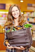 Attractive smiling woman in supermarket holding shopping bag full of vegetables