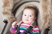 Beautiful Baby Girl In A Pink Knitted Dress Sitting In A Stroller