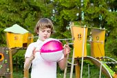 Cute Child Playing With A Pink Ball On A Colorful Playground