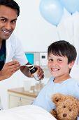 Sonriente médico examina a un niño con su padre