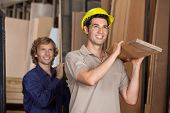 Happy carpenters carrying wooden plank on shoulders while looking away in workshop