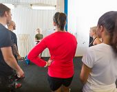 Group of athletes listening to instructor at cross training gym