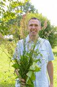 Man herbalist picking up wild herbs